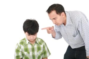 A father is threatening his little boy with a finger